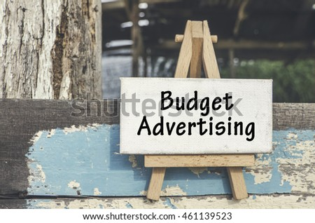 inspiration and success concept, word BUDGET ADVERTISING over dirty white canvas frame and wooden easel at sunny day.wooden cottage background. faded look and color tone with grain effect.