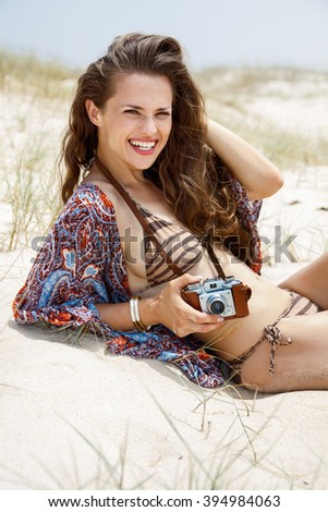 Inspiration captured on wild and wonderful beaches. Smiling bohemian young woman with retro photo camera sitting on a white beach
