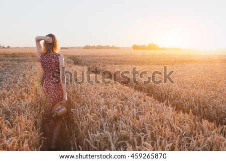inspiration or waiting concept, happy beautiful young woman in sunset field, dream
