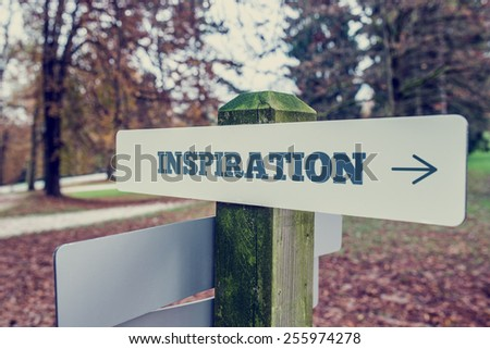 Inspiration signboard on a wooden post with a right pointing arrow outdoors against greenery in a faded retro image. - stock photo