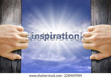 Inspiration text in the blue sky behind hand opening a wooden door. - stock photo