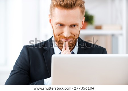 Inspiration while working. Happy bearded businessman working on computer and smiling while sitting at his working place