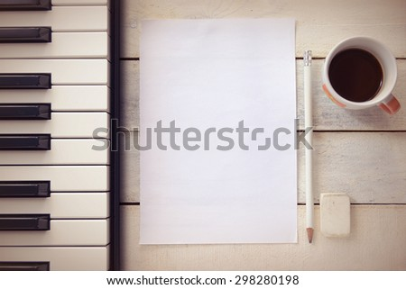 Inspirational background with a piano on a wooden table while composing. Score sheet, a pencil and a cup of coffee for the music composer, Top view and a copy space for editor's text. - stock photo