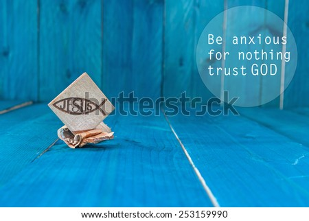 Inspirational motivating quote saying that God has everything in control. Christian fish symbol carved in wood and blue vintage wooden background - stock photo