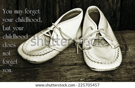 Inspirational quote about childhood by Michael Dibdin with a closeup of vintage baby shoes on a grunge wood backdrop.
