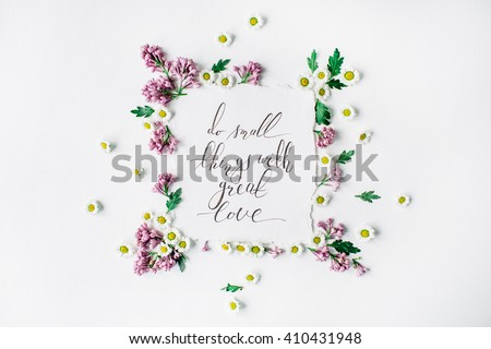 """inspirational quote """"Do small things with great love"""" written in calligraphy style on paper with wreath frame with lilac and chamomile isolated on white background. flat lay, overhead view, top view - stock photo"""