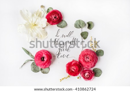 "inspirational quote ""Do small things with great love"" written in calligraphy style on paper with pink, red roses, ranunculus, white tulip and leaves isolated on white background. Flat lay, top view - stock photo"