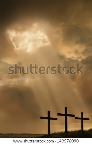 Inspirational religious photo illustration of three large crosses on the top of a hill, a breaking storm, and light beams breaking through the clouds, shining towards the crosses. - stock photo