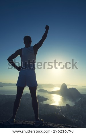 Inspirational silhouette of athlete in white sport uniform standing with champion arm raised in front of Rio de Janeiro Brazil sunrise skyline overlook at Sugarloaf Mountain - stock photo