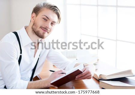 Inspired author. Handsome young man in shirt and suspenders writing something in note pad and smiling at camera while sitting at his working place - stock photo