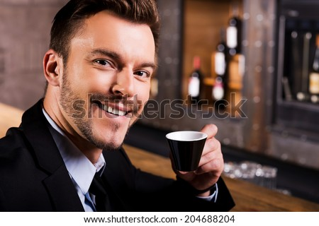 Inspired by cup of fresh coffee. Confident young man in formalwear drinking coffee and smiling while sitting at the bar counter - stock photo