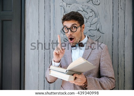 Inspired funny young man in round glasses reading book and having an idea - stock photo