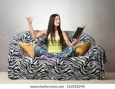 Inspired girl sitting on the sofa and reciting a poem - stock photo