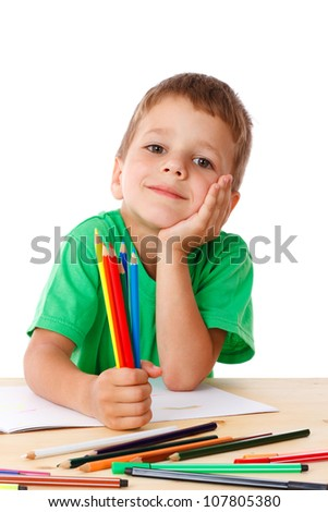 Inspired little boy at the table draw with crayons, isolated on white - stock photo