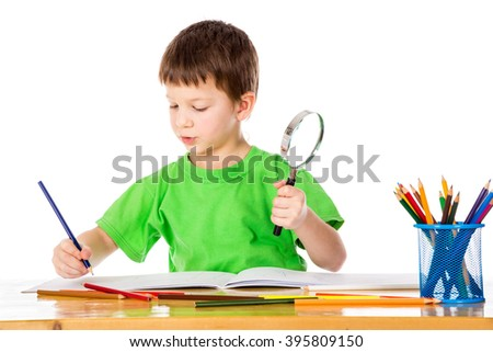 Inspired little boy at the table draw with pencils and magnifier in hands, isolated on white - stock photo