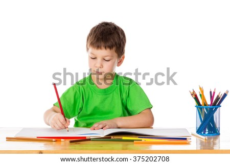 Inspired little boy at the table draw with pencils, isolated on white - stock photo