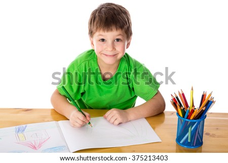 Inspired little boy at the table draw with pencils, isolated on white