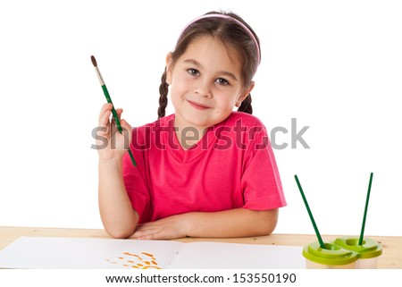 Inspired little girl with paintbrush on the table, isolated on white - stock photo