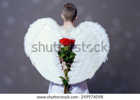 Inspired, romantic man-angel with a bouquet of red roses. Valentine's day. Love concept. - stock photo