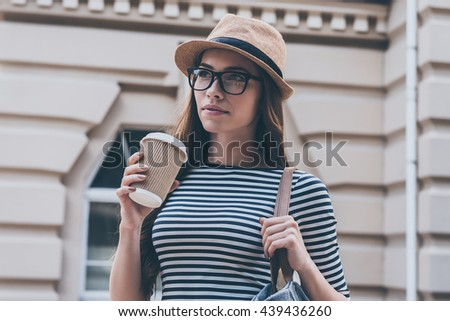 Inspired with cup of fresh coffee.  Beautiful young woman holding coffee cup and looking away while standing outdoors  - stock photo