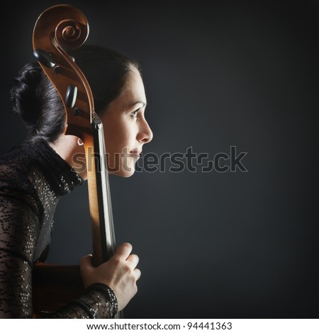 Inspired woman profile cello. Beautiful cellist classical musician with musical instrument - stock photo