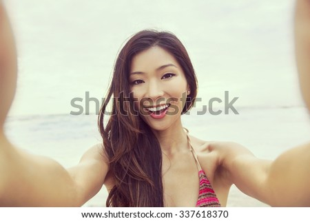 Instagram effect photograph of Asian young woman or girl in bikini, taking vacation selfie photograph at the beach  - stock photo