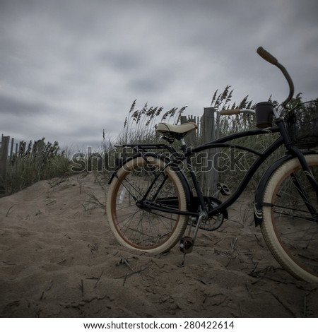 Instagram filtered image of a vintage bicycle and sand dunes on the beach