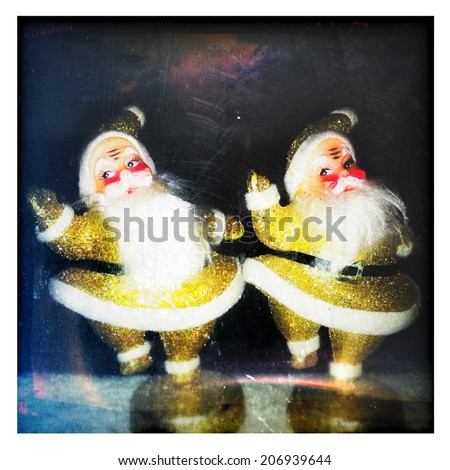 Instagram filtered style image of two glittery gold vintage dancing Santa Claus - stock photo