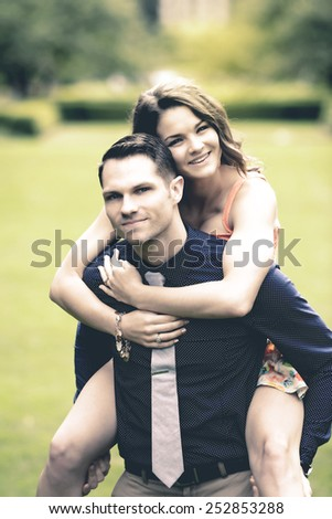 Instagram look of an image showing a handsome young man carrying his fiance on his back in a garden setting - stock photo
