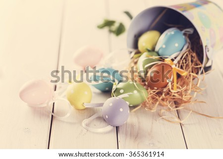 Instagram looking image of Ester decor eggs over white wooden table. Color toning, filters, selective focus, shallow depth of field, rustic style - stock photo
