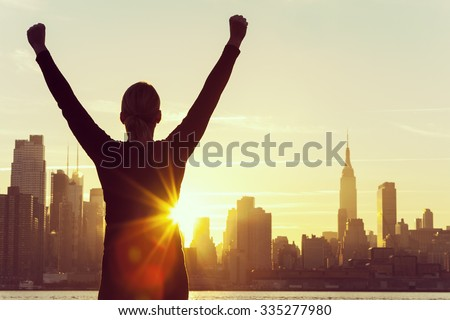 Instagram style filter silhouette of a successful woman or girl arms raised celebrating at sunrise or sunset in front of the New York City Skyline - stock photo