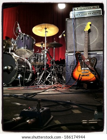 Instagram style image of a guitar and drums on stage - stock photo