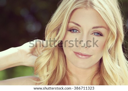 Instagram style portrait of naturally beautiful woman in her twenties with blond hair and blue eyes, shot outside in sunlight with a natural green background