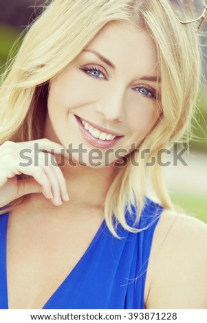 Instagram style portrait portrait of naturally beautiful woman in her twenties with blond hair and blue eyes, shot outside in natural sunlight - stock photo