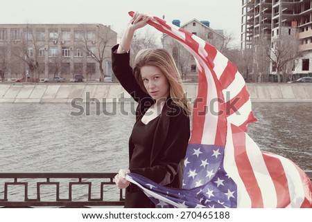 Instagram sutro style image of blond women with weaving stars and stripes in her hands near river fence in city with copyspace. - stock photo