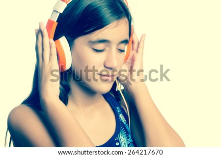 Instagram toned small teenage girl listening to music on her headphones - stock photo