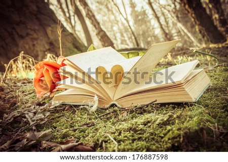 instagram vintage effect, love autumn - open book with heart and rose on the moss in the forest - stock photo