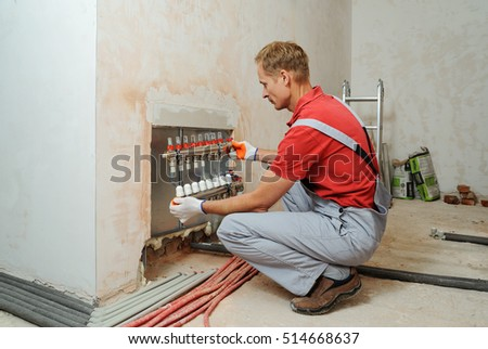 Installation Of Home Heating A Worker Holds The Underfloor Manifold