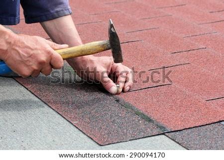 Installation of roof asphalt shingles - stock photo