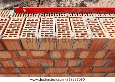 Installed bricks with construction level - stock photo
