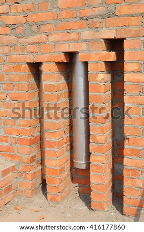 Installed in brick wall metal chimney for fireplace. Stainless steel chimney stove pipe installation. - stock photo