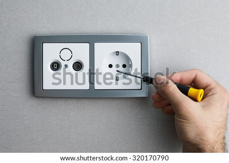 Installing a silver wall-mounted AC power socket with a screwdriver on a grey wall, renovating home. Close up view. - stock photo