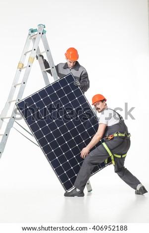 installing alternative energy photovoltaic solar panels white background - stock photo