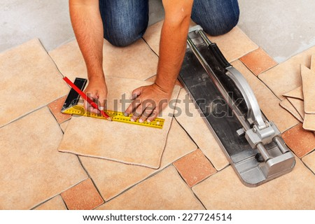 Installing ceramic floor tiles - measuring and cutting the pieces, closeup - stock photo