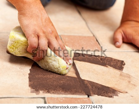 Installing ceramic floor tiling - testing the color of joint material, closeup - stock photo