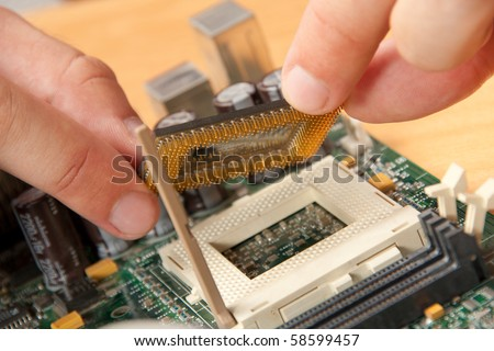 Installing computer processor to motherboard - stock photo