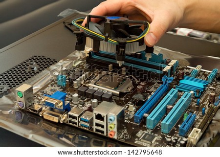 Installing cooler onto the motherboard - stock photo