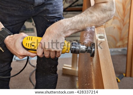 Installing doorknob, prepares door for knob and dead bolt, drilling bore holes  through door using hole saw drill bit, close-up. - stock photo