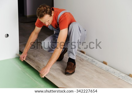 Installing laminate flooring. Worker lining boards to each other
