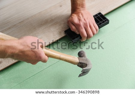 Installing laminate flooring. Worker lining boards to each other - stock photo